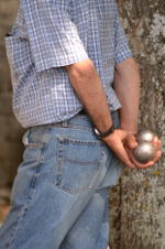 Man holding a pair of boules, steel balls about the size of tennis balls, behind his back.