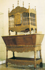 A panetiere, an openwork bread box made of wood spindles, sitting on a kneading table.