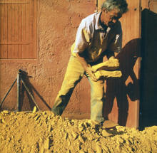 An ochre worker moving slabs of yellow ochre, the same color as his dusty clothing