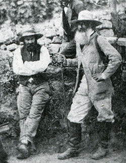 Historic photo of Pissarro and Cezanne, both bearded, both wearing slouch hats, standing, black and white.