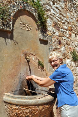 Susan Vreeland washing her hands after a delicious lunch in place de la Mairie, Roussillon: Photo Copyright Marcia M. Mueller