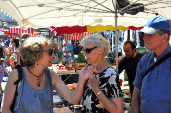 Susan Vreeland  engages a woman from Rooussillon in conversation at the market: Photo Copyright Marcia M. Mueller